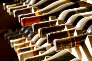 Бутылка вина в горизонтальном положении покрытая пылью в стойке