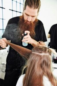Мастер наносит термозащиту на волосы