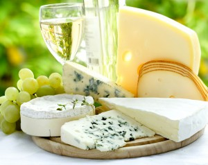 Сыр на подносе с белым вином и виноградом